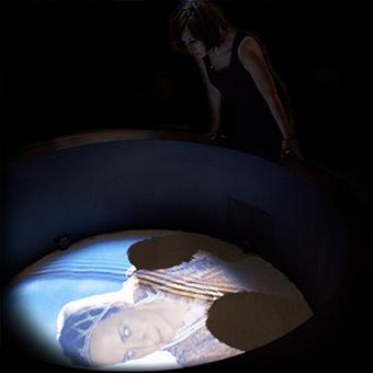 Installazione multimediale del pozzo con immagine del volto di una donna