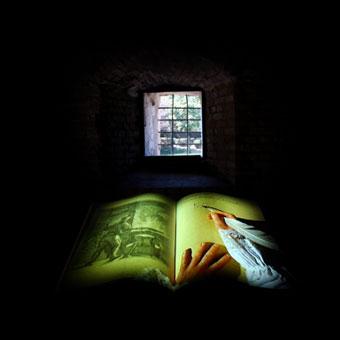 Installazione multimediale con libro antico davanti alla finestra della torre nel castello di Formigine