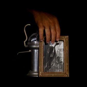 Una mano tocca un portafoto e un oggetto di metallo, appartenuti a Trilussa