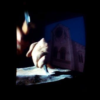 Mani che scolpiscono ed edificio religioso in pietra