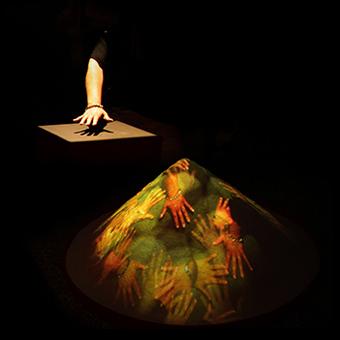 Proiezione di mani su un cumulo di sale e mano illuminata su tavolo touchscreen