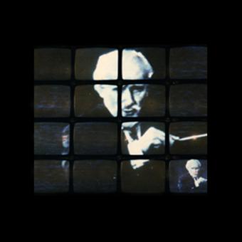 Parete di monitor con immagini di Arturo Toscanini che dirige La Scala