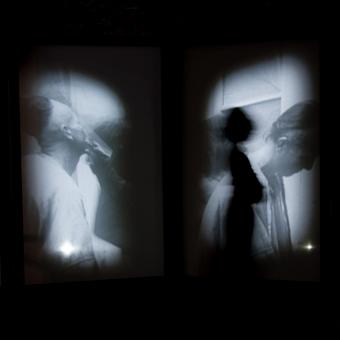 Proiezioni in bianco e nero di figure orientali e silhouette scura di una figure femminile in piedi