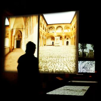Silhouette davanti ad allestimento espositivo con proiezioni di un chiostro