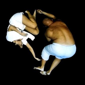 Due corpi rannicchiati in una proiezione a pavimento interattiva