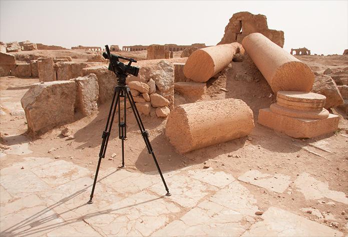 Telecamera di fronte a colonne e reperti archeologici