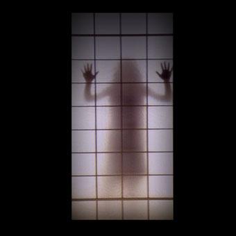 Figura di donna che si intravede dietro il vetro di una casa