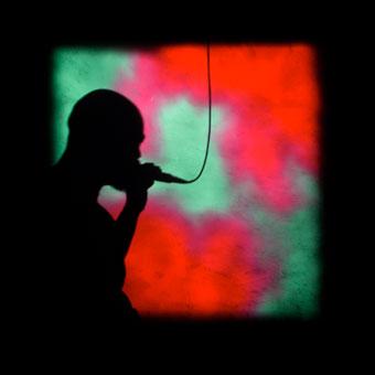 Silhoutte di visitatore al microfono davanti a una proiezione in rosso e verde