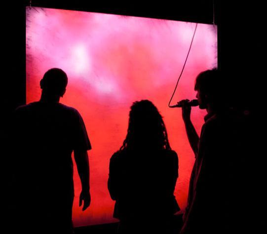 Variazioni Magenta - silhouette di visitatori con microfono davanti allo schermo