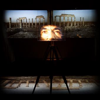 Installazione video con rovine classiche e primo piano di occhi