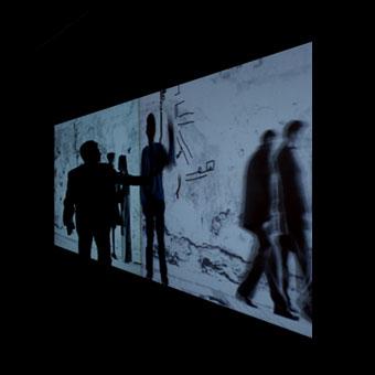 Proiezione interattiva a parete con personaggi che camminano davanti a un muro