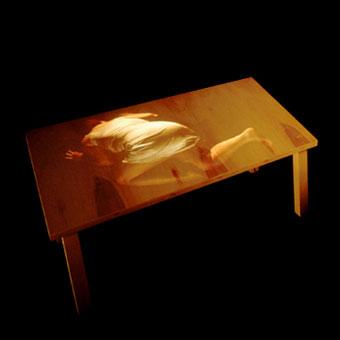 Figura proiettata su tavolo di legno interattivo