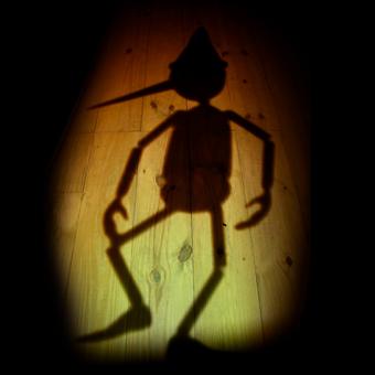 Ombra del burattino Pinocchio su un pavimento di legno