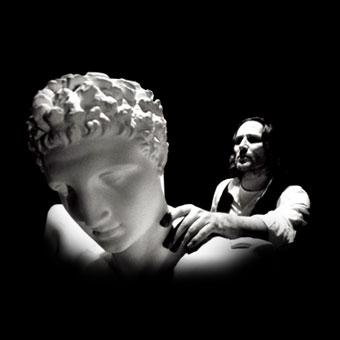 """Moni Ovadia con una statua classica in una scena di """"Delfi (studio per suono, voce, video e buio)"""""""