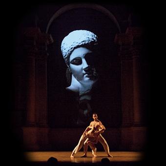 Due danzatori sul palco del teatro con videoproiezione di scultura classica