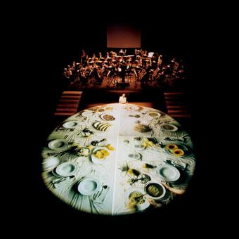 Scena con orchestra e grande scrivania rotonda con proiezioni video