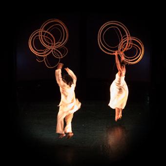Due danzatori interagiscono con videoproiezioni di forme circolari