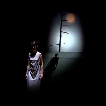 Scena di Neither, con una donna vestita di bianco in piedi e proiezioni sullo sfondo