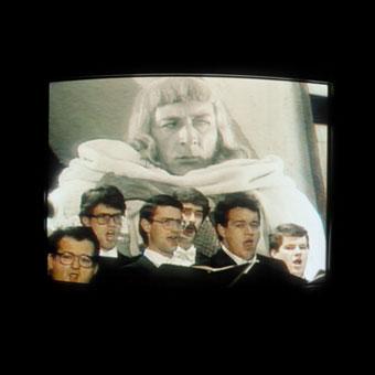 """Coro con alle spalle proiezioni video, dall'opera """"Alexander Nevskij"""""""
