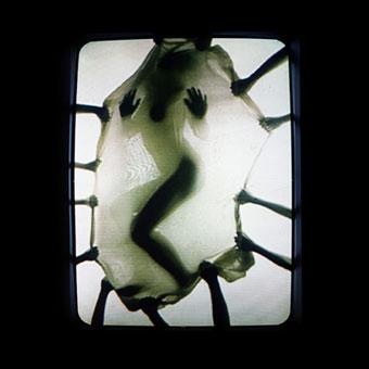 Videoproiezione con sagoma di un corpo femminile dietro una supericie tesa da diverse braccia