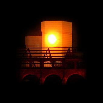 Proiezione notturna di un sole che sorge sulla Fabbrica del Vapore