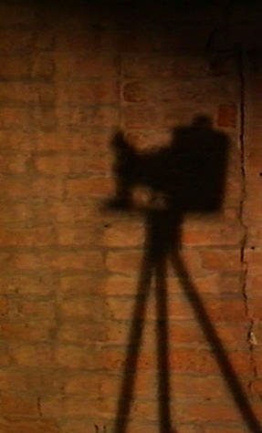 Ombra di telecamera a silhouette su parete di mattoni